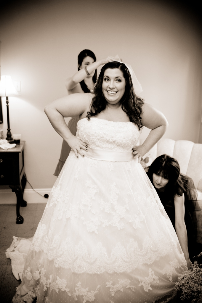 bride putting on gown photo
