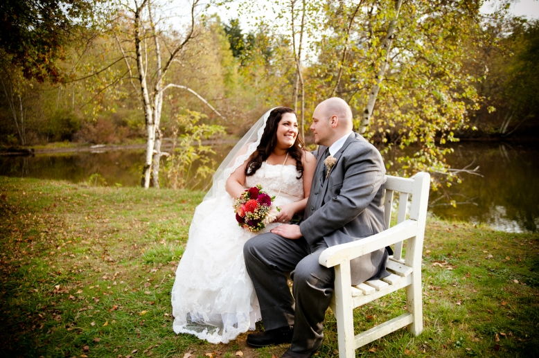 bride and groom on a bench in front of pond